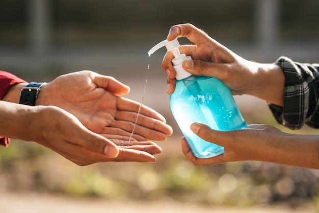 Handen bij de gelfles om handen te wassen en knijp in voor anderen om handen te wassen. Gratis Foto