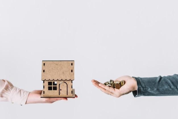 Handen bijsnijden met munten en huis Gratis Foto