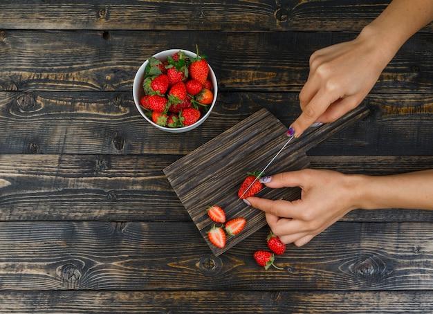 Handen die aardbeien met mes op houten raad snijden Gratis Foto