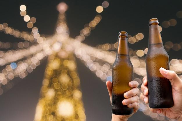 Handen die bierflessen houden en gelukkig van oogsttijd samen genieten aan rammelende glazen bij openluchtpartij Premium Foto
