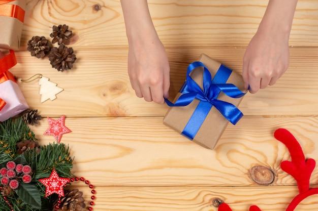 Handen die de gift van kerstmis inpakken op houten Premium Foto