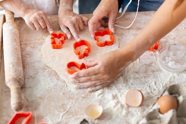 Handen die deeg met koekjevormen snijden Gratis Foto