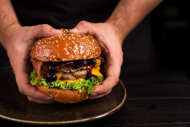 Handen die dubbele hamburger met kaas houden Gratis Foto