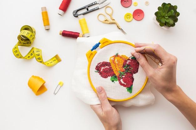 Handen die een leuk fruitontwerp op witte achtergrond naaien Gratis Foto