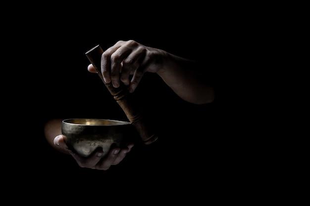 Handen die een oude tibetaanse zingende kom spelen. zwarte achtergrond. muziektherapie. Premium Foto