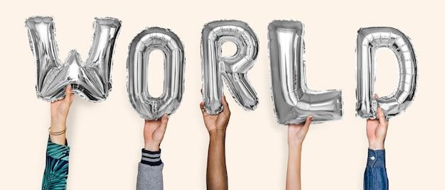 Handen die het woord van wereldballons tonen Gratis Foto