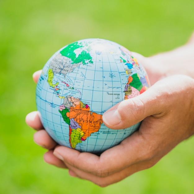 Handen die kleine bol houden tegen groene achtergrond Gratis Foto
