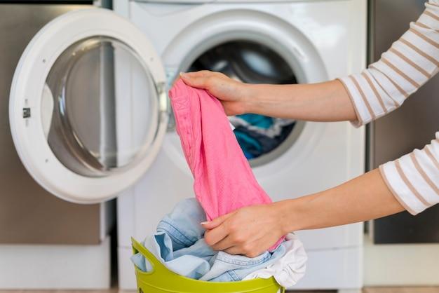 Handen die kleren in wasruimte uitrekken Gratis Foto