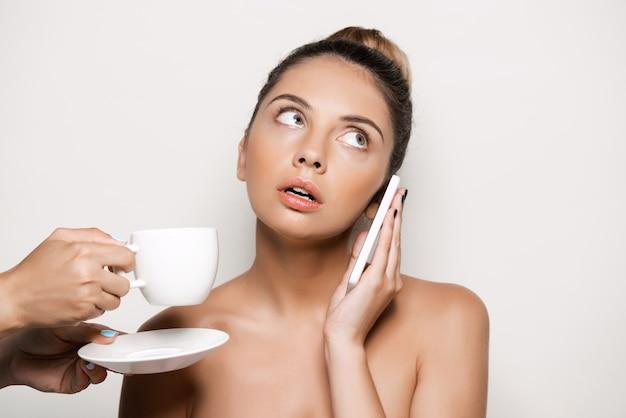Handen die kop van koffie aanbieden aan vrouw die op telefoon spreekt Gratis Foto