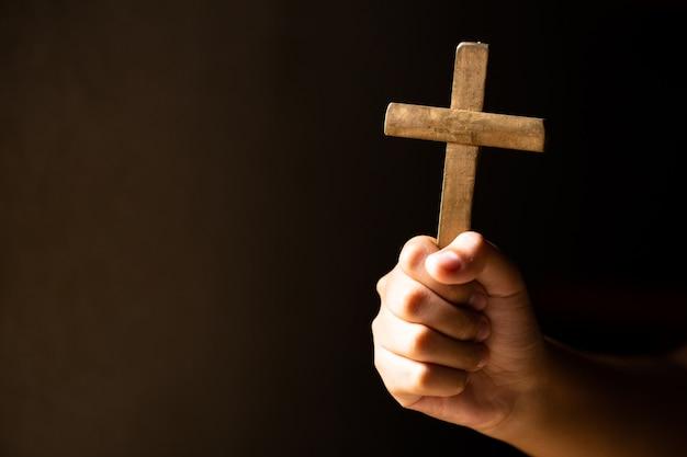 Handen die kruis houden tijdens het bidden. Gratis Foto