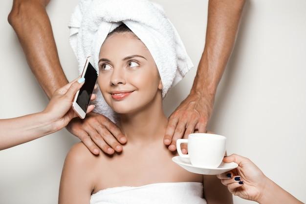 Handen die massage doen, telefoon en koffie geven aan mooie vrouw Gratis Foto