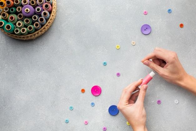 Handen die met naaigaren en knopen werken Gratis Foto