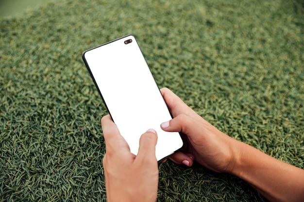 Handen die moderne telefoon met model houden Gratis Foto
