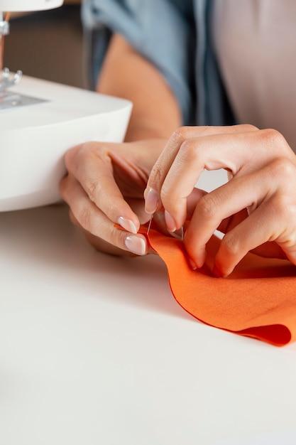 Handen die oranje stoffenclose-up naaien Premium Foto