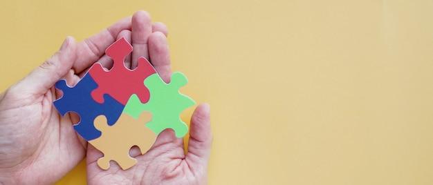 Handen die raadselpuzzel, concept van de geestelijke gezondheid, de voorlichtingsdag van het wereldautisme houden Premium Foto