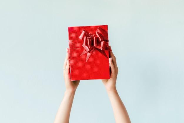 Handen die rode gift op duidelijke achtergrond houden Gratis Foto