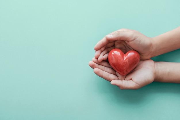 Handen die rood hart op blauwe achtergrond houden Premium Foto