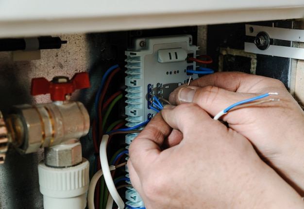 Handen die signaalkabels schakelen in de verwarming van het huis. Premium Foto
