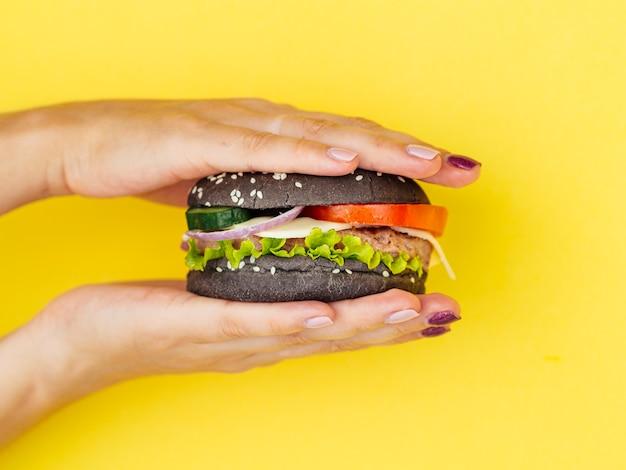 Handen die smakelijke hamburger met gele achtergrond drukken Gratis Foto