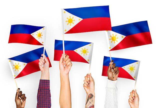 Handen die vlaggen van de filippijnen golven Gratis Foto
