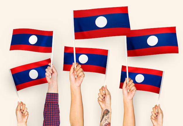 Handen die vlaggen van de pdr van laos golven Gratis Foto