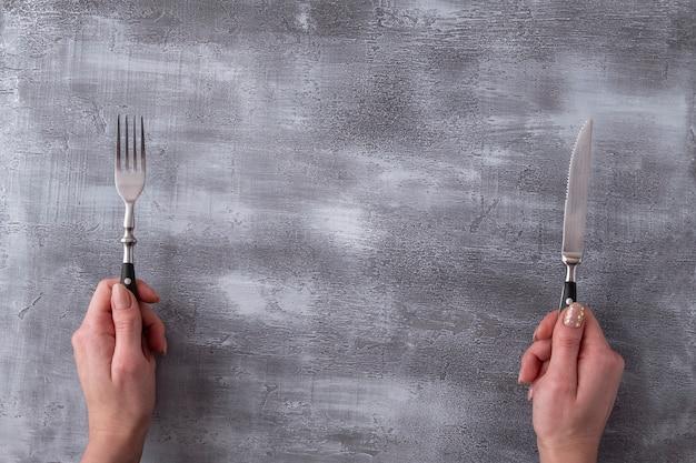 Handen die vork en mes op grijze oppervlakte houden. . bovenaanzicht Premium Foto