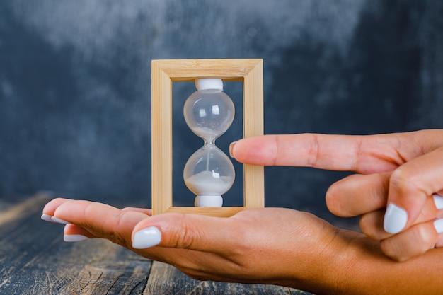 Handen die zandloper houden en tijd tonen Gratis Foto