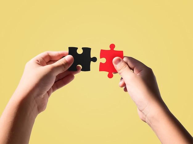 Handen die zwarte en rode kleurenpuzzels houden die op mooie pastelkleur worden geïsoleerd. Premium Foto