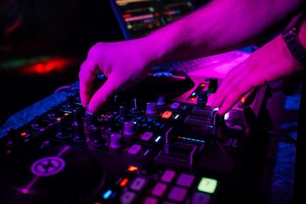 Handen dj spelen en mixen van muziek op muziekcontroller op een feestje Premium Foto