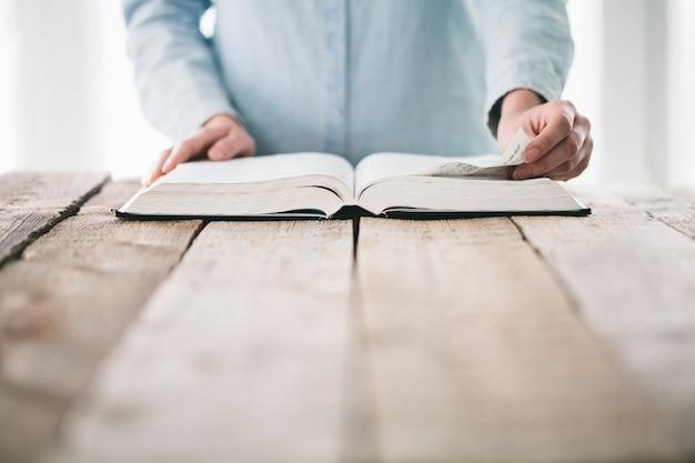Handen draaien de pagina van een bijbel Premium Foto