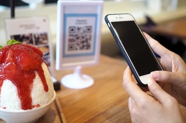 Handen gebruiken de telefoon om de qr-code te scannen om kortingen van binsu-bestellingen in het café te ontvangen. Premium Foto