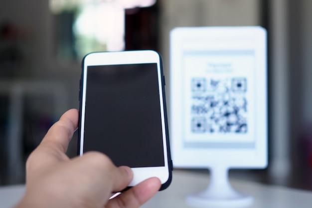 Handen gebruiken de telefoon om qr-codes te scannen om kortingen op aankopen te ontvangen. Premium Foto