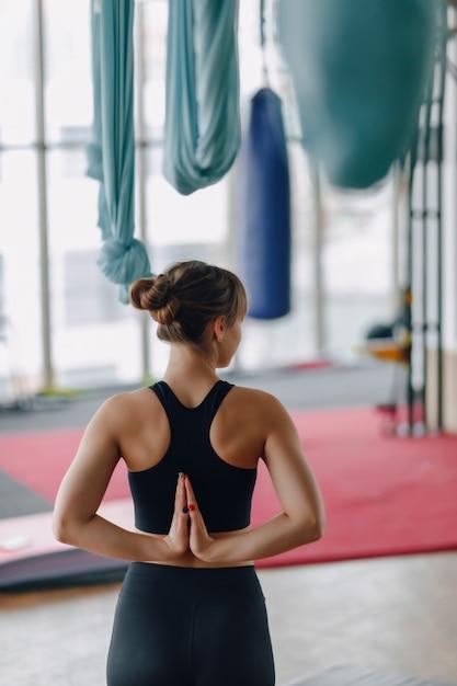 Handen gevouwen achter haar rug, meisje in de sportschool tijdens yogales Gratis Foto