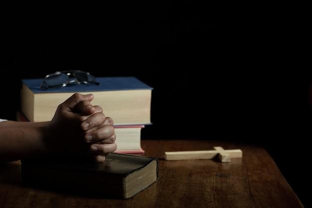 Handen gevouwen in gebed op een heilige bijbel in de kerk Gratis Foto