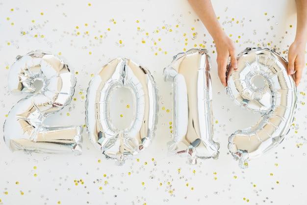 Handen in de buurt van ballonnen nummers tussen confetti Gratis Foto