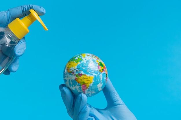 Handen in medische handschoenen desinfecteren de continenten van zuid- en noord-amerika, naar een model van de wereld, het concept van de strijd tegen coronavirus Premium Foto