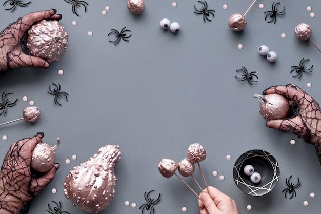 Handen in mesh-handschoenen met roze pompoenen, ogen en spinnen, plat met kopie-ruimte. Premium Foto