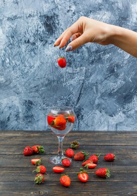 Handen met aardbeien op een houten bord Gratis Foto