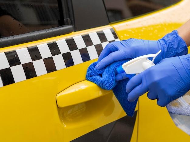 Handen met chirurgische handschoen schoonmaken auto deur handvat Premium Foto