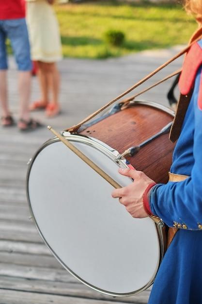 Handen met drumsticks en een grote drum nationale jurk Premium Foto