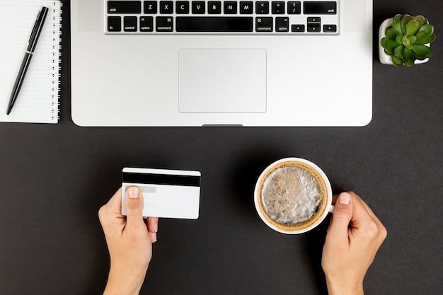 Handen met een koffiekopje en een creditcard Gratis Foto
