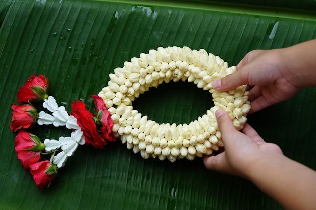 Handen met een slinger gemaakt van jasmijn en rozen op groene bladeren Premium Foto