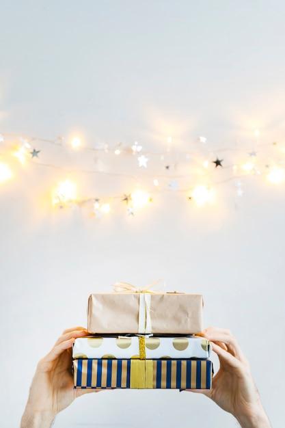 Handen met geschenkdozen in de buurt van fairy lights en ornament-sterren Gratis Foto