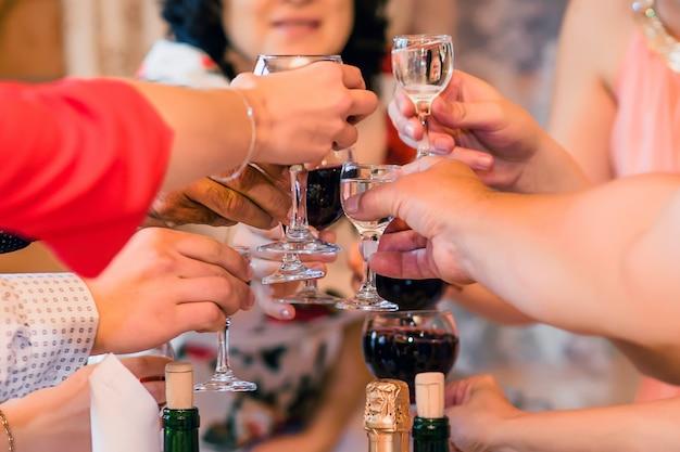 Handen met glazen wijn en wodka groep vrienden op een feestje Premium Foto