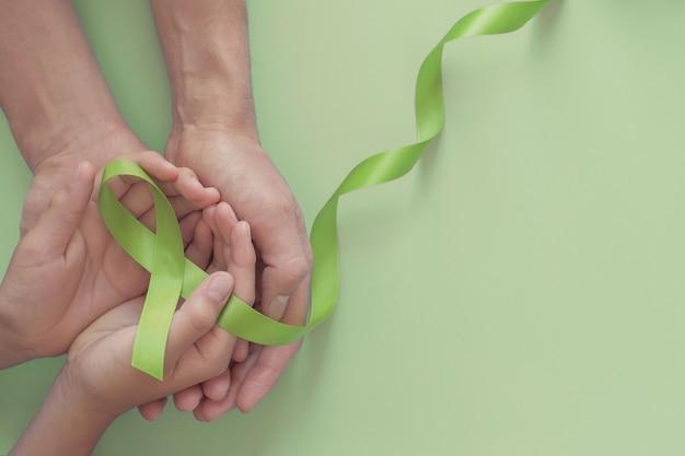 Handen met groen lint, wereld geestelijke gezondheidsdag Premium Foto