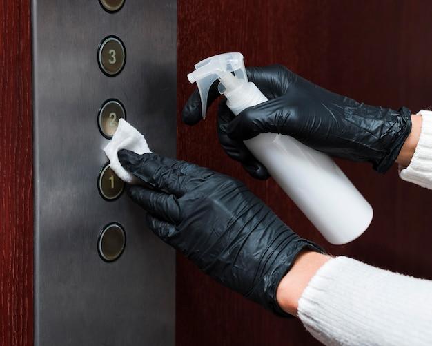 Handen met handschoenen die liftknoppen desinfecteren Gratis Foto