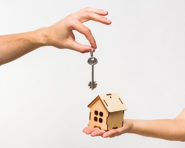 Handen met houten huis en sleutel Gratis Foto