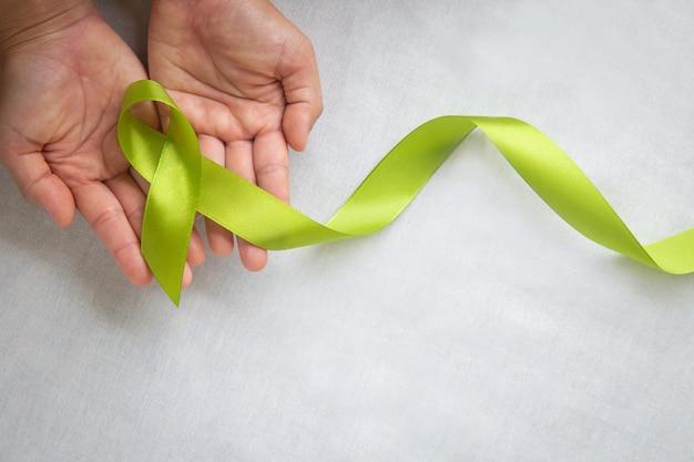 Handen met licht limoen groen lint op witte stoffen achtergrond met kopie ruimte. werelddag voor geestelijke gezondheid en symbool voor lymfoombewustzijn. Premium Foto