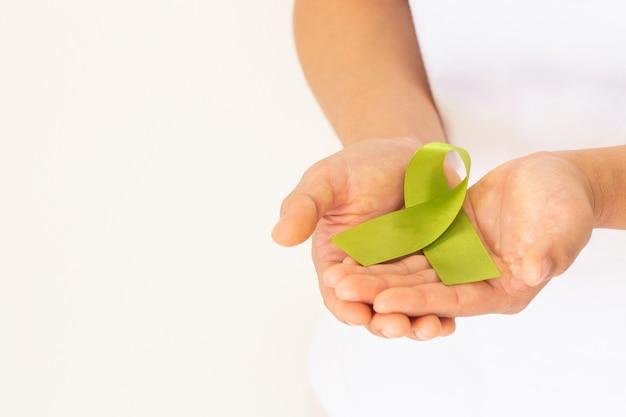 Handen met licht limoengroen lint wereld dag van de geestelijke gezondheid en lymfoom bewustzijn symbool Premium Foto
