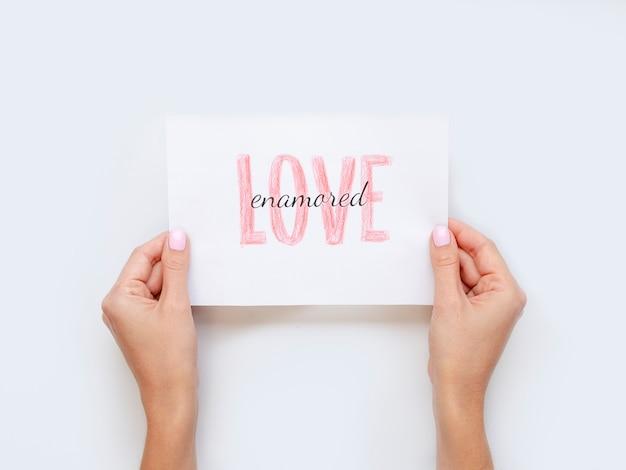 Handen met liefde papier plat lag Gratis Foto